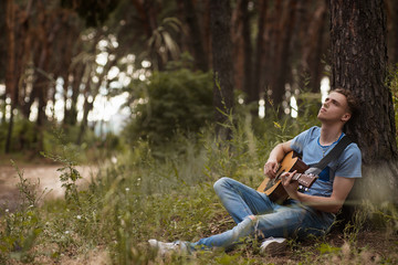 Pensive man playing guitar forest concept. Alone on the nature. Lifestyle of artist.