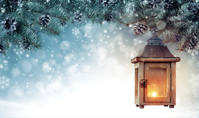 Christmas background with spruce branches and wooden lantern.