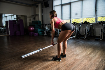 Girl does a deadlift with a blank recordable rod in the hall of fitness.