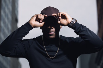 Brutal man rapper with cap posing in city