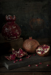 Close-up of the fruit of a pomegranate, broken into pieces. Still life in a dark key. Selective focus, shallow depth of field, background