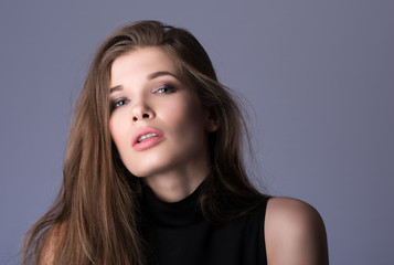 Portrait of beautiful young woman with long hair in black clothes
