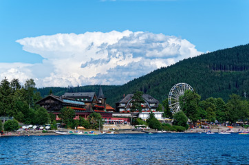 Beautiful view on the promenade, traditional houses and ferris wheel over the Titisee - most famous lake in Black Forest national park, Germany.