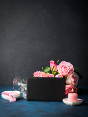 Valentine's day concept and greeting card. Romantic date invitation with pink candles, roses, hearts and black board for writing greetings