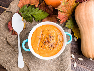 Photo from above of orange pumpkin soup on linen fabric