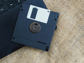 Floppy disk placed on laptop keyboard jute texture background