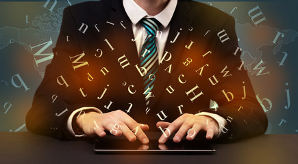 Man typing in formal clothing and letters around