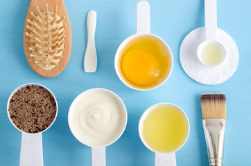 Sour cream (greek yogurt), raw egg, ground coffee with brown sugar and olive oil in small plastic scoops - ingredients for preparing diy masks, scrubs and moisturizers. Homemade cosmetics.