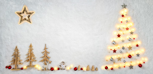 Christmas symbols creatively shaped with lights and wooden ornaments on snow background