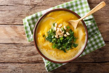 spicy Thai pumpkin soup with peanuts and cilantro close-up in a bowl. Horizontal top view