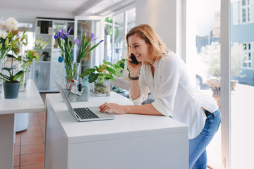 Florist talking on mobile phone and using laptop