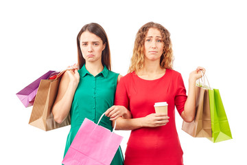 Portrait of two female friends holding multi-colored shopping bags