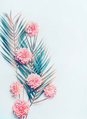 Wall Mural - Creative layout with tropical palm leaves and pastel pink flowers on  turquoise blue desktop background, top view, place for text, vertical