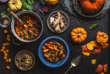 Vegan pumpkin stew dish with spinach served in bowl with spoon on dark kitchen table background with pot and ingredients.  Healthy seasonal food and clean eating concept