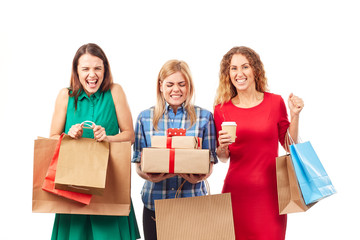Portrait of three shopaholic girlfriends holding shopping bags and gift boxes