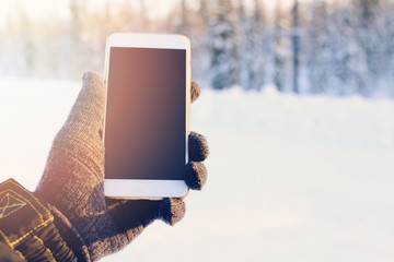 Smartphone in hand on the winter forest background