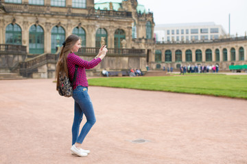 Young woman with long hair use smartphone in european old city