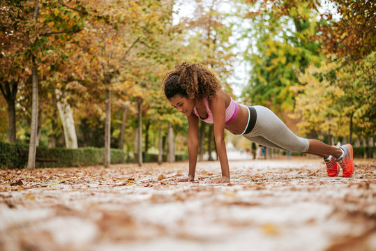 Fitness woman doing pushups in autumn park.