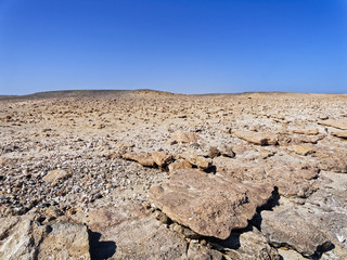 A Barren desert landscape under a cloudless blue sky