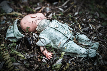 abandoned old broken baby doll rots in scary forest