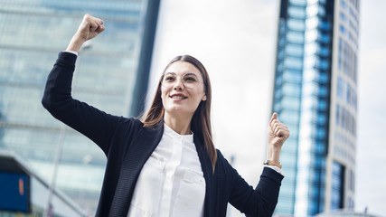 Successful business woman with arms up outdoors