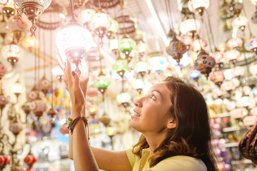 Woman shopping at Istanbul Bazaar and choosing turkish traditional souvenir lamp