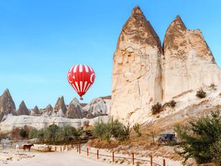 Hot air balloon flying over horse corral in Cappadocia