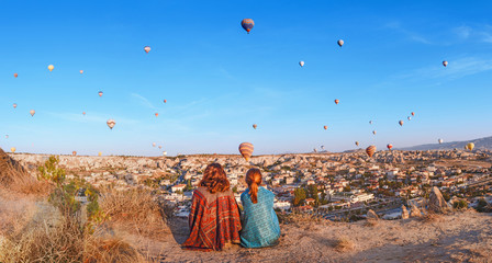 Couple of friends travelers enjoying valley view with wonderful balloons flight over Cappadocia valley in Turkey