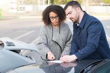 Man and woman filling an insurance car form