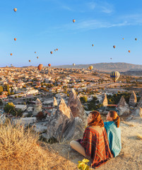 Two young females looking at balloons above valley, , Turkey
