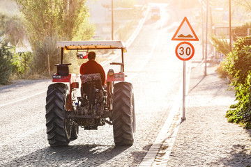 Tractor rides on the pavement road in the sunlight