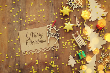 Top view image of christmas festive decorations next to note on old wooden background.