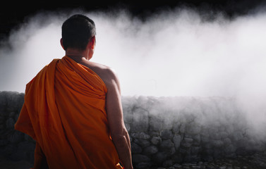 Monk meditating in the open air with cloud of smoke