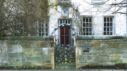 Picturesque Old House with decorated gate, surrounded by trees at Edinburgh city, Scotland, UK