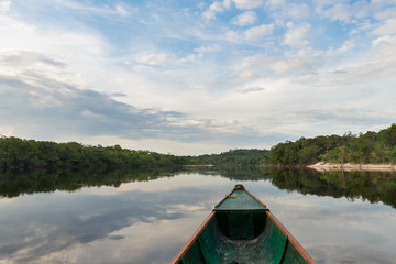 Reflections of sky and trees on the waters of the Sipapo river, in the amazon jungle.