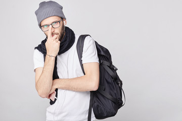Close up isolated portrait of serious European male traveler wears trendy hat, white shirt with bag, holds finger on nose, looks pensively as tries to find solution in difficult transport situation.