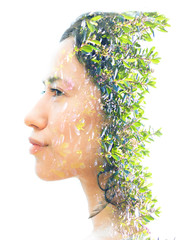 Double exposure of a young ethnic latina beauty combined with bright green leaves gives a dissolving effect