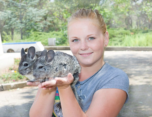 Portrait of blonde girl with chinchillas. Girl holding two chinchillas