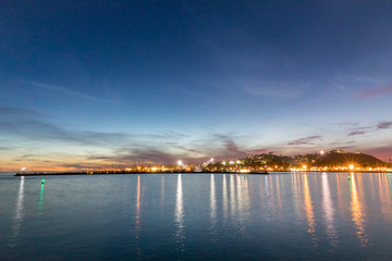 Beautiful night view from the shore over water to a city lights reflected on water in evening