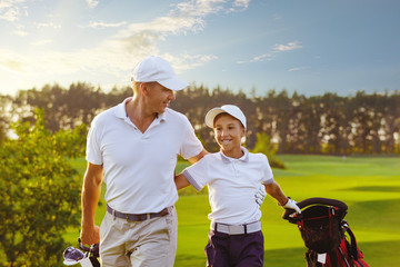 Papiers peints Golf Happy man with his son golfers walking on perfect golf course at summer evening