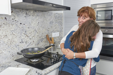 A mother and her teenage daughter bond by cooking vegan food together in the kitchen.