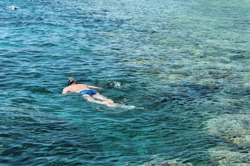 Woman photographer diving into water of Red sea