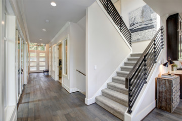 Hallway features a staircase with gray carpet runner