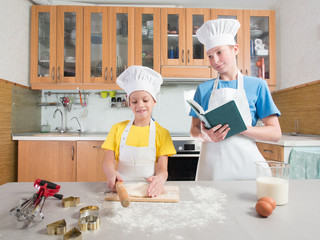 Little girl in the form of a chef with an apron and a cap blinks the dough with her hands, and next to her is her adult brother and reads a book on the background of the kitchen with a table