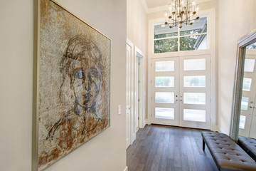 White sophisticated foyer entry design with glass doors.