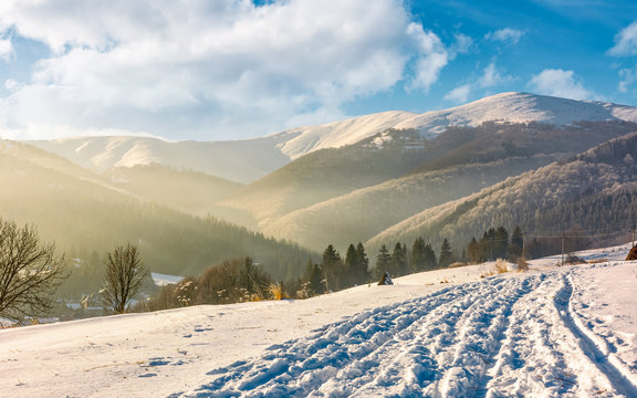 snowy mountain ridge above the rural area. lovely countryside winter scenery.