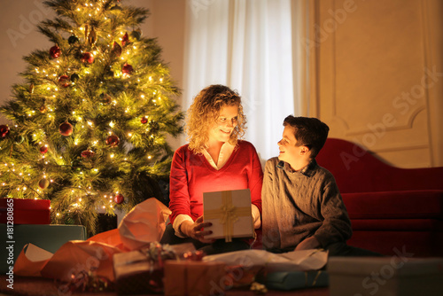 Sweet mother looking at christmas gifts with her son\