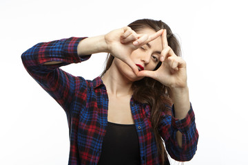 Cropped portrait of styish young woman with dark long hair making frame with hands as if taking picture, looking at camera through space between finger. People, photographing and creativity concept