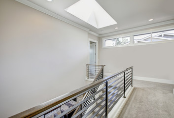 Second floor landing features skylight over the staircase