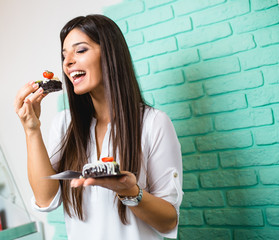Beautiful young woman enjoying in delicious glazed and decorated donuts.